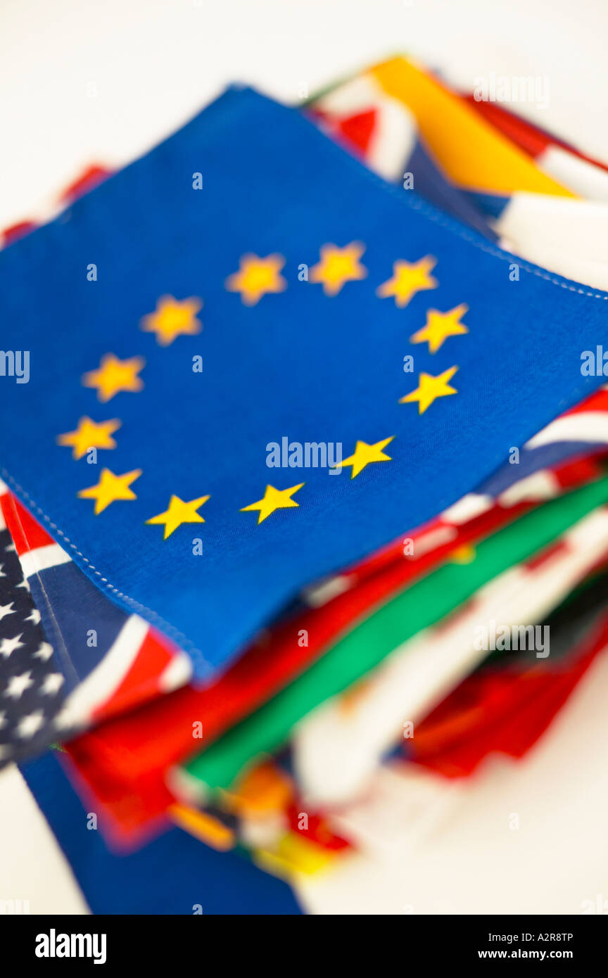 European Union Flag Yellow Stars on Blue Background on top of pile of international country flags - Stock Image