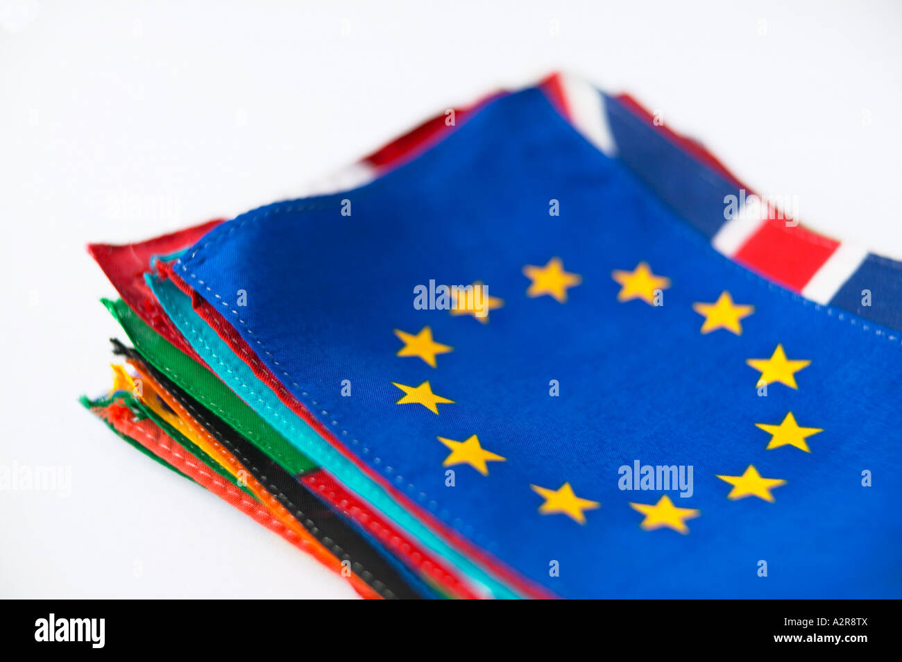 European Union Flag Europe EEC laying on top of pile of National Flags white background - Stock Image
