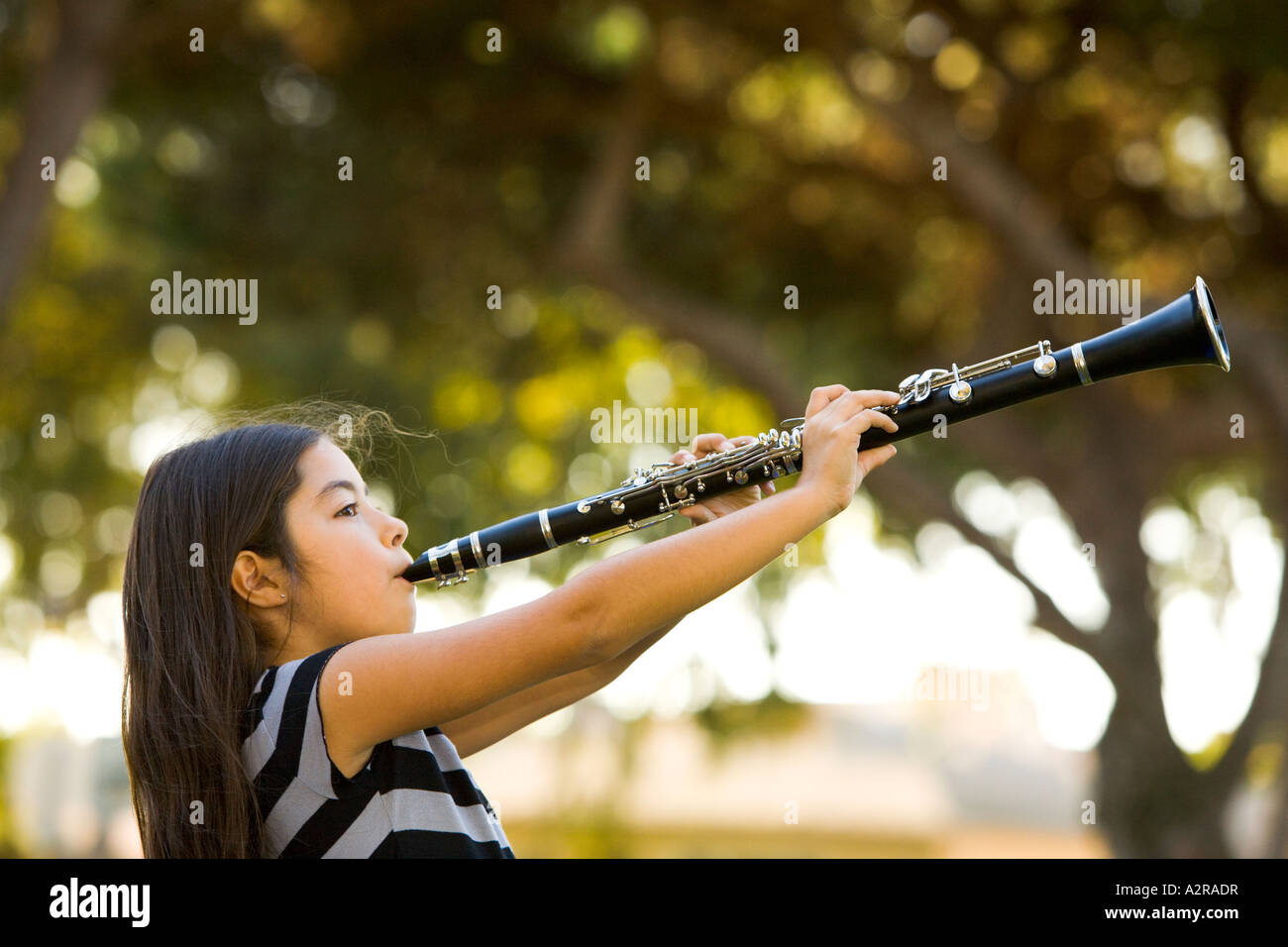 A young girl ten years old plays her clarinet in a park Los Angeles California Model Released - Stock Image