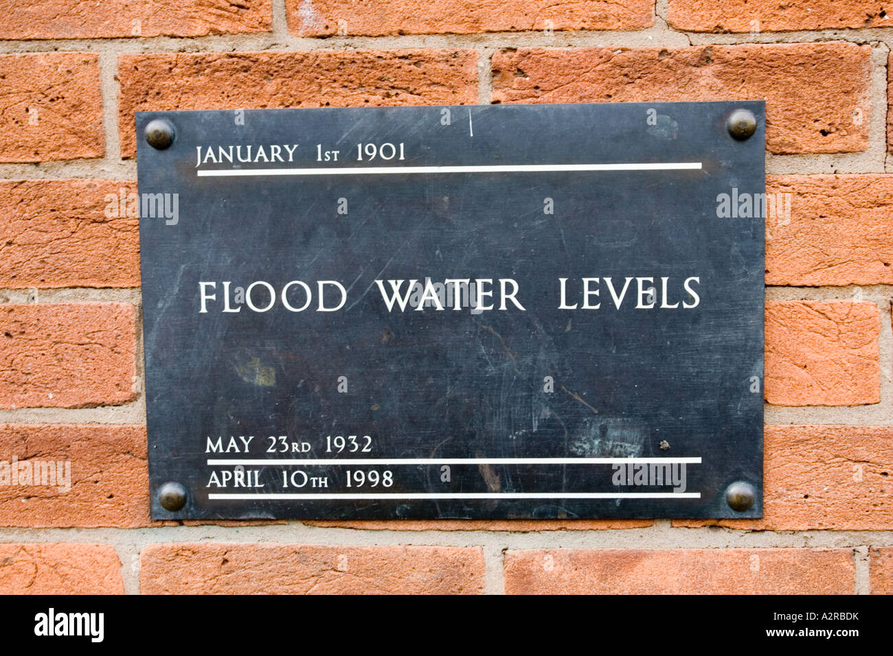 Brass plate displaying high flood levels on wall of house in Stratford upon Avon UK - Stock Image