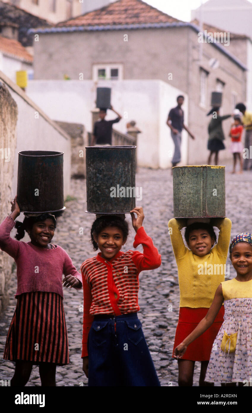 girls carrying water cans on the square on the island Saô Vicente on the Cap Verde islands - Stock Image