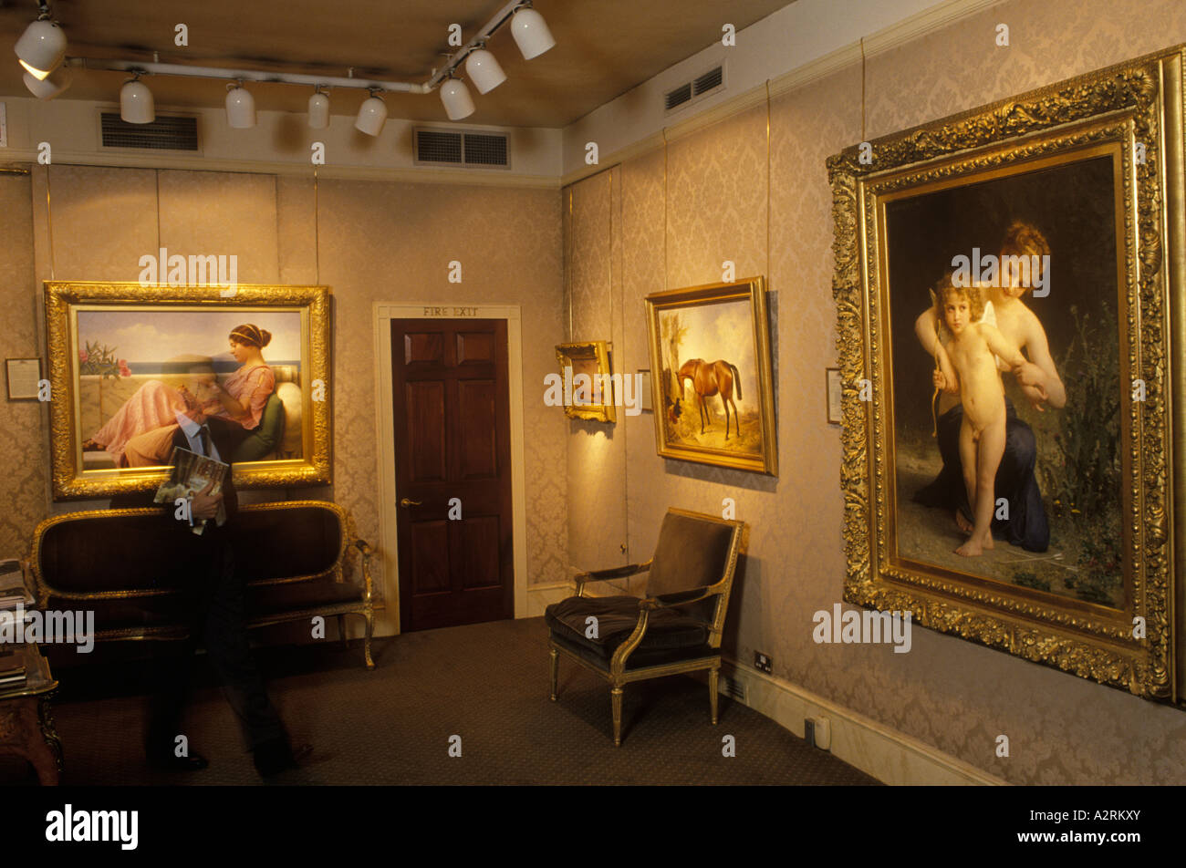 Art dealer in his  gallery with paintings Belgravia Art Gallery London England. - Stock Image
