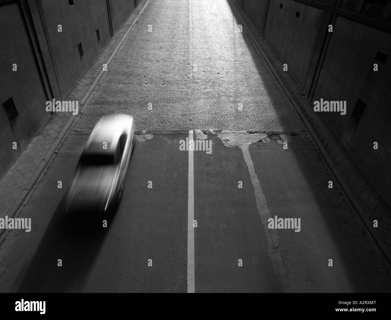 Silver car Mercedes speeding into tunnel Brussels Belgium motion blur monochrome black and white - Stock Image