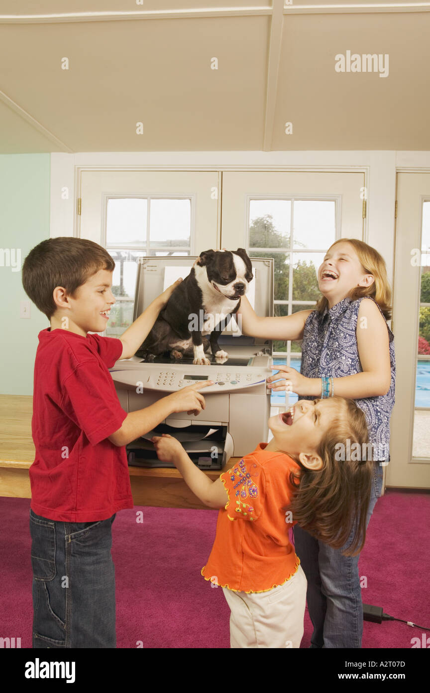 Three kids faxing a dog - Stock Image