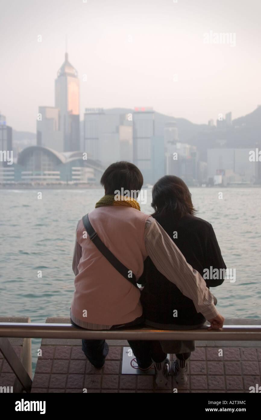 A couple enjoying the view of Hong Kong and Victoria Harbour from Tsim Sha Tsui Kowloon Hong Kong Stock Photo