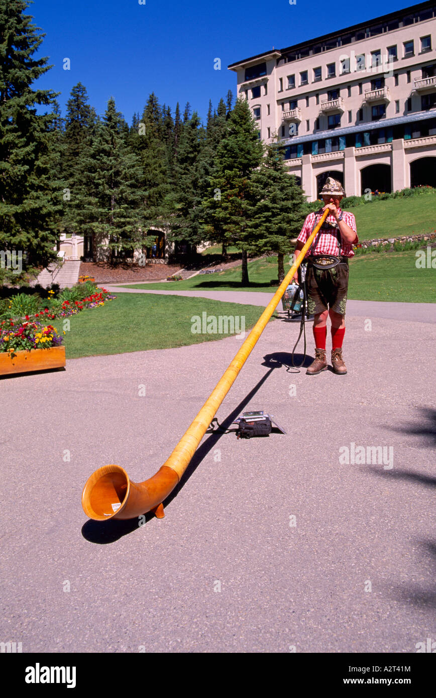 An Alpenhorn Player performing at Lake Louise in Banff National Park in the Canadian Rockies Alberta Canada - Stock Image