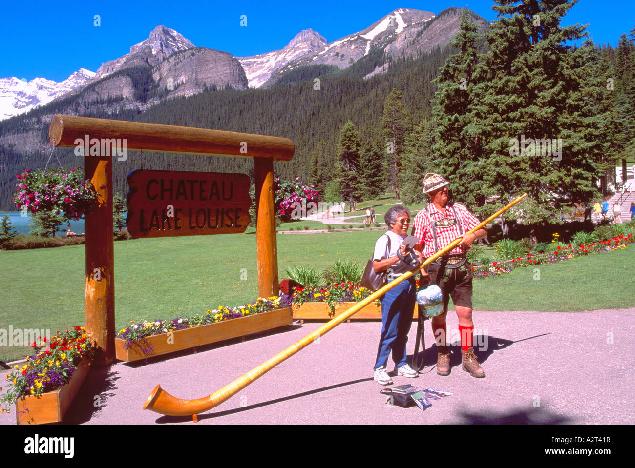 An Alpenhorn Player posing with Tourist at Lake Louise in Banff National Park in the Canadian Rockies Alberta Canada - Stock Image