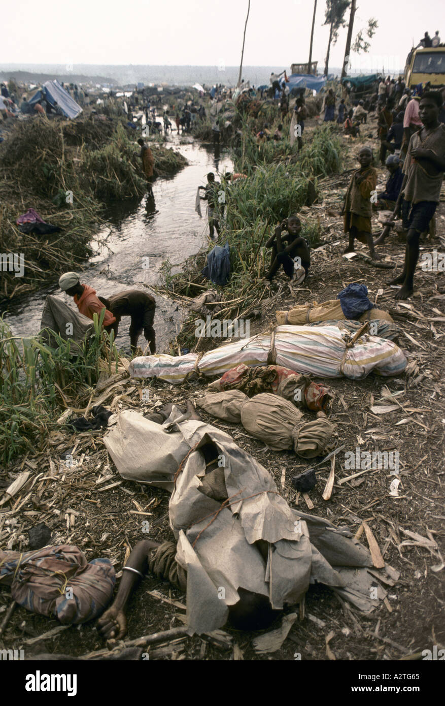 rwandan refugees july 1994 dead bodies of children adults wrapped in cloth paper laid out on the banks of a stream where people are washing clothes katali refugee camp - Stock Image