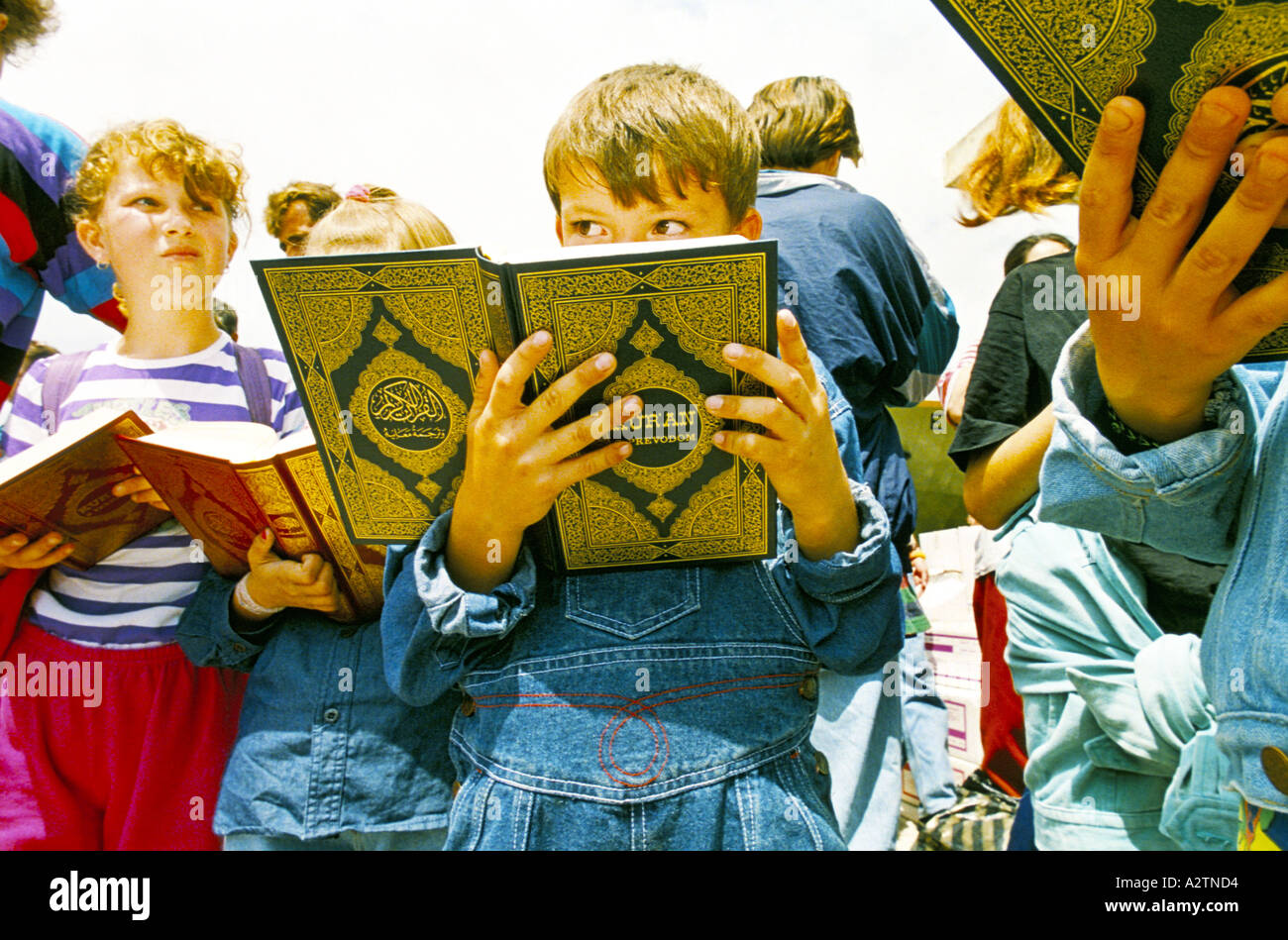 central bosnia june 1995 refugees arrive from macedonia to return to sarajevo children reading the koran - Stock Image