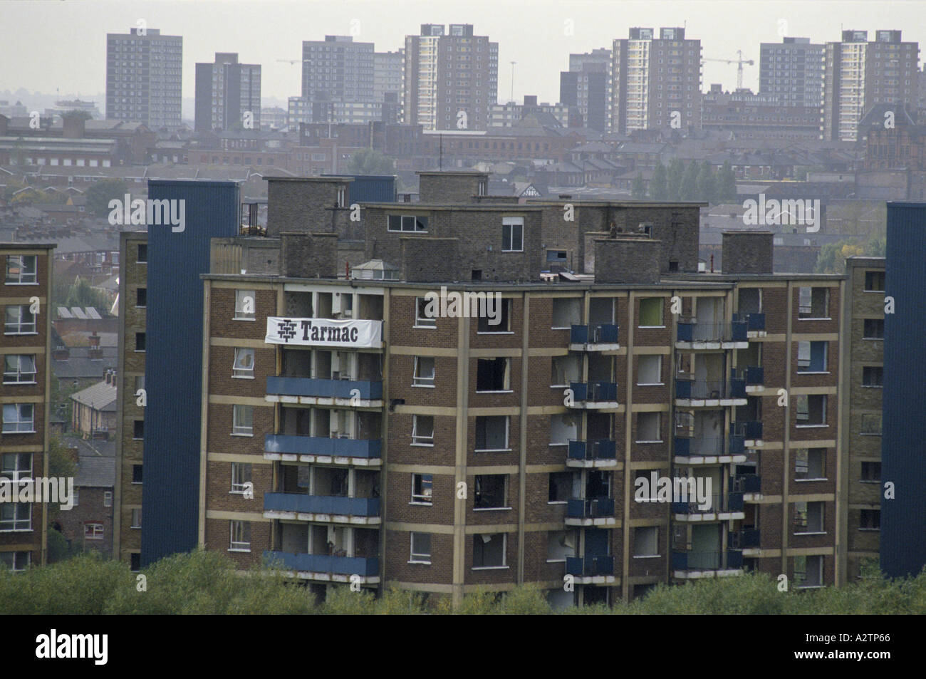 emptied tower block waiting to be demolished skyline with high rise housing blocks as background manchester - Stock Image