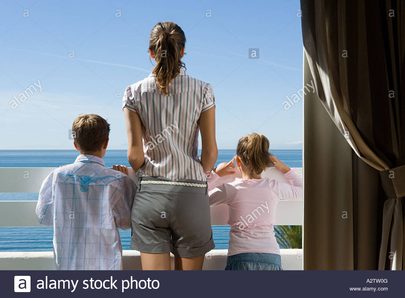 Mother on balcony with children - Stock Image