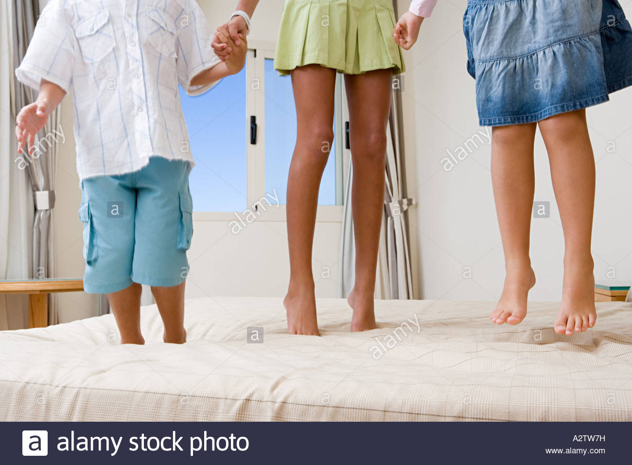 Children jumping on bed - Stock Image