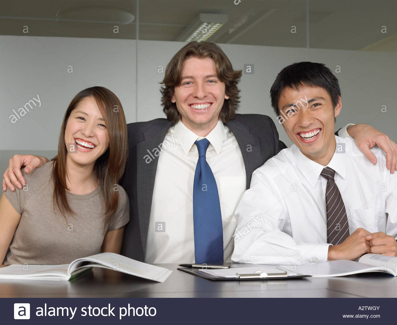Office worker with arm around colleagues Stock Photo