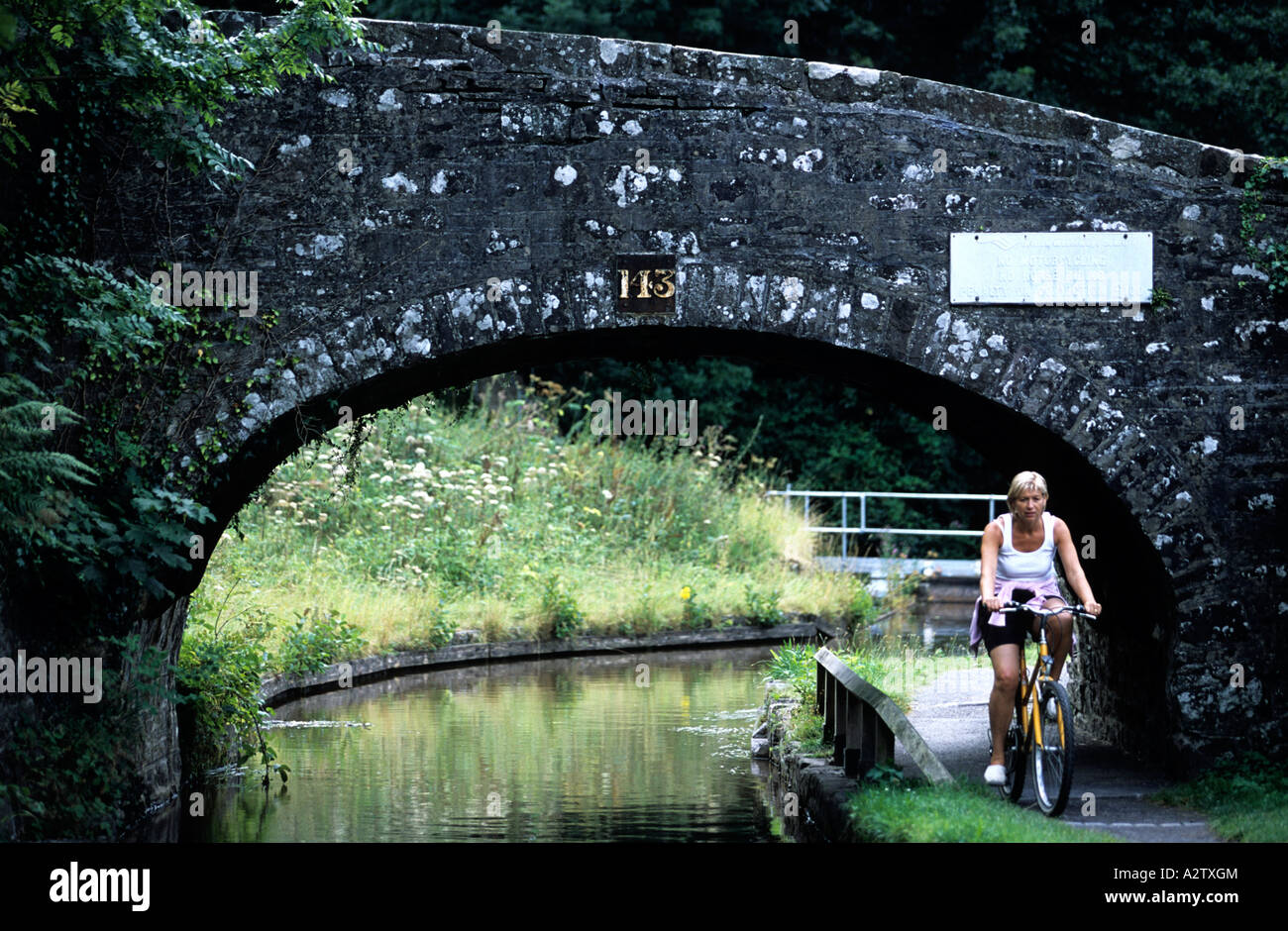 Cyclists on towpath on the Monmouthshire & Brecon canal at Talybont-on-Usk, Brecon, Powys, Wales, GB - Stock Image