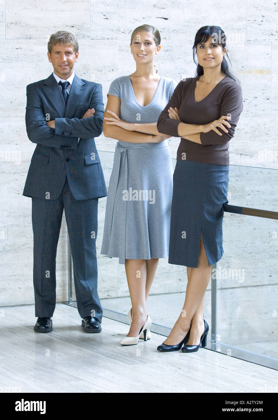 Three business executives standing with arms folded, full length portrait - Stock Image