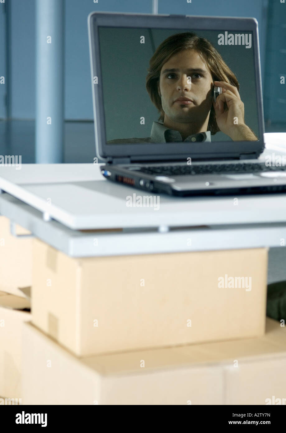 Image of man using cell phone reflected in laptop screen - Stock Image