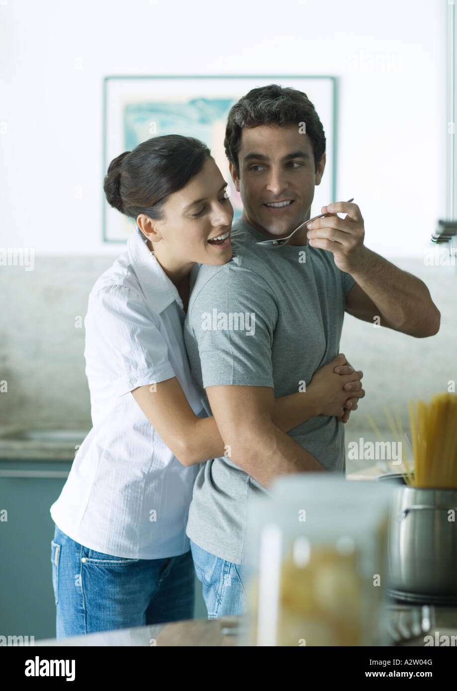 In kitchen, woman holding man around waist as man reaches back with spoon for woman to taste - Stock Image