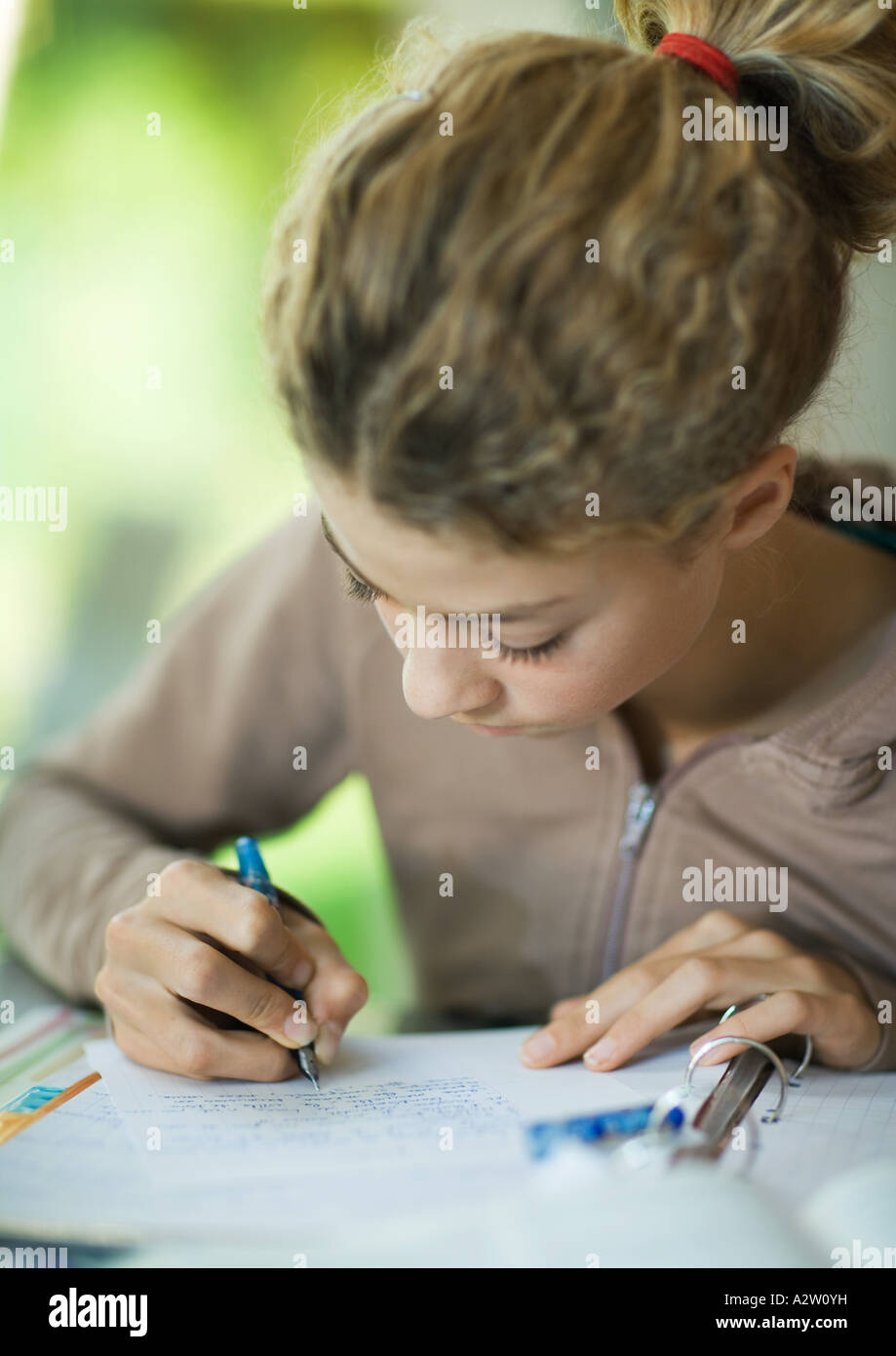 Preteen girl doing homework - Stock Image