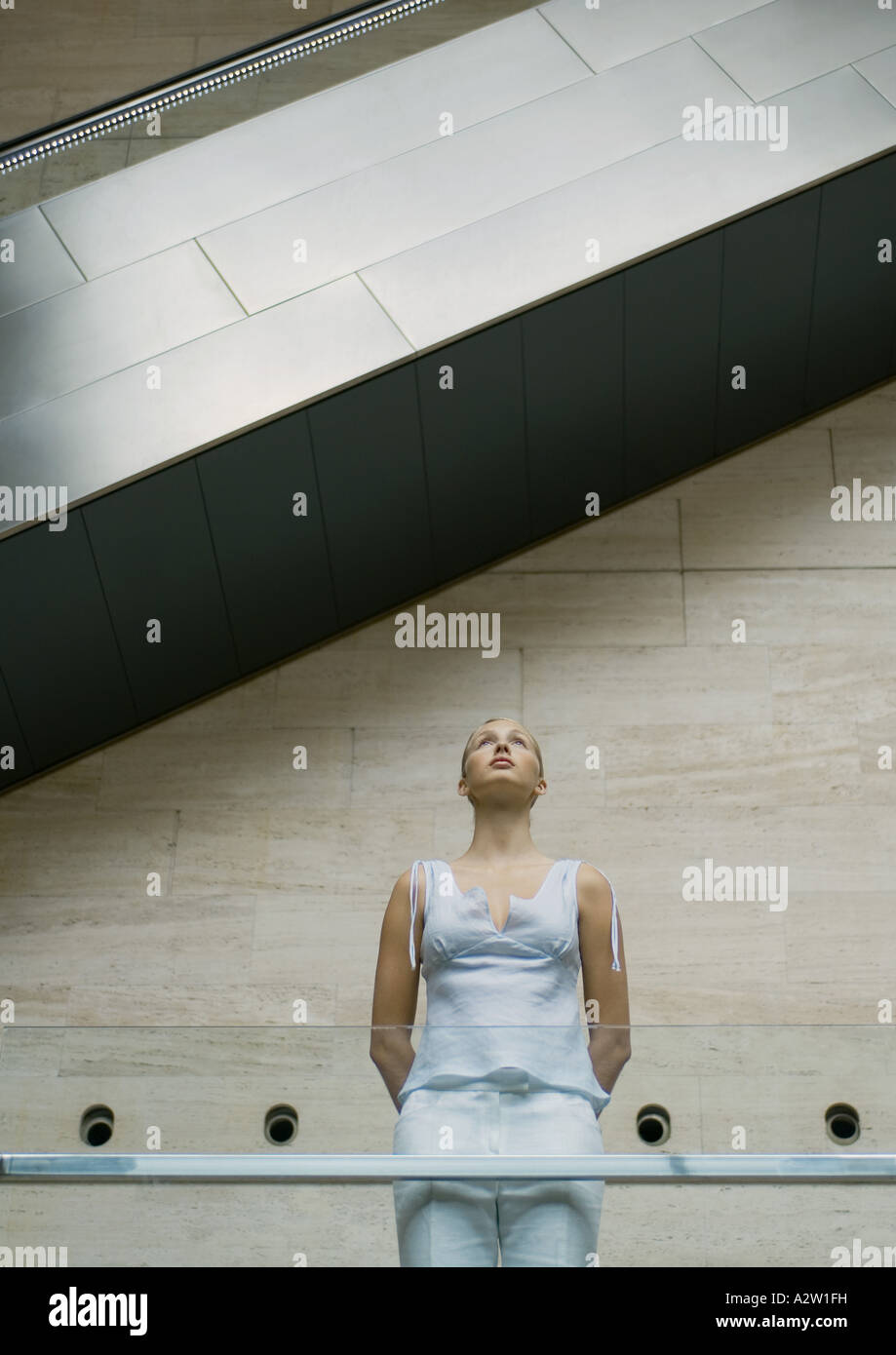 Woman standing under escalator, low angle view - Stock Image