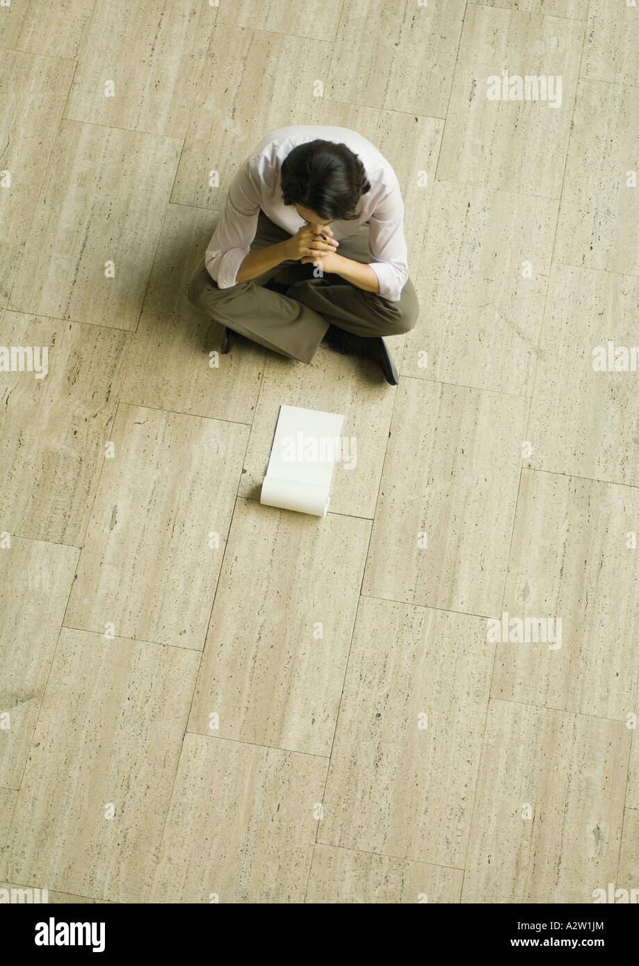 Man sitting on floor with blank pad of paper, high angle view - Stock Image