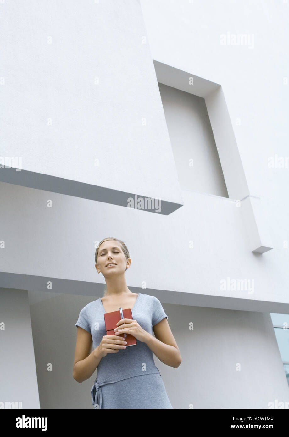 Woman standing in front of building, holding closed book, eyes shut, low angle view - Stock Image