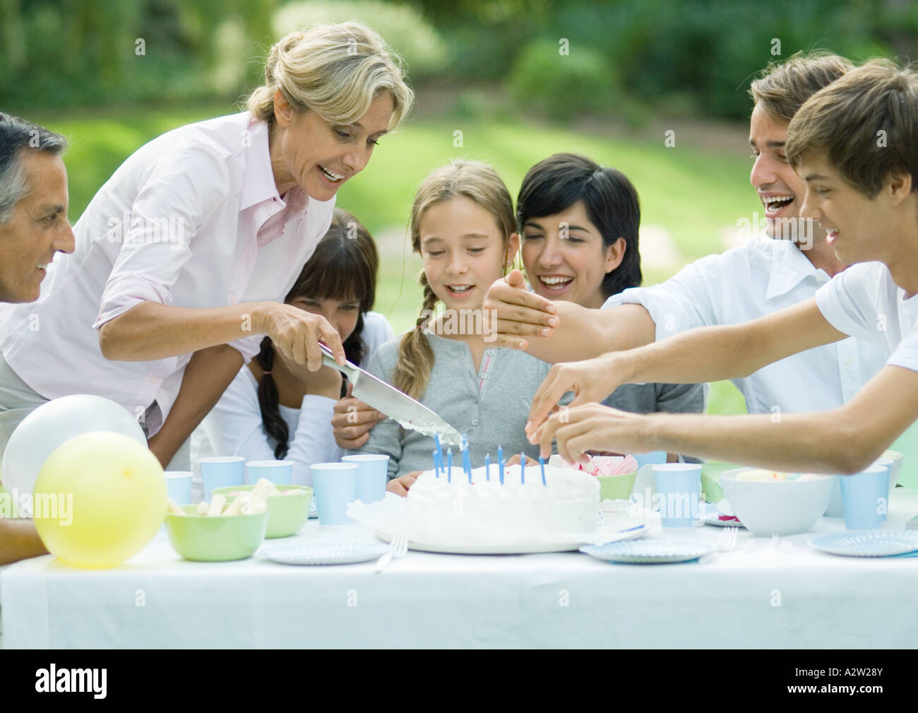 Outdoor birthday party mature woman cutting birthday cake Stock