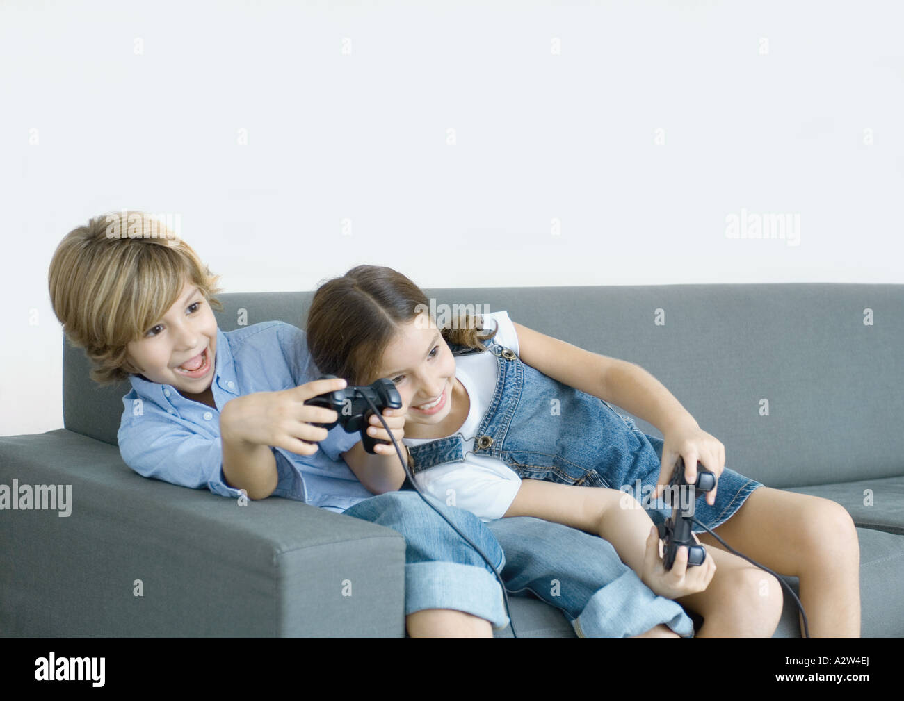 Children sitting on sofa, holding joysticks - Stock Image