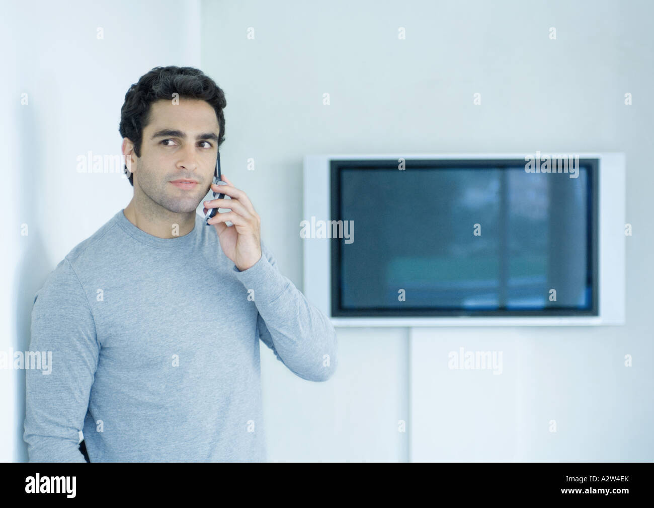 Man using cell phone, widescreen TV in background - Stock Image