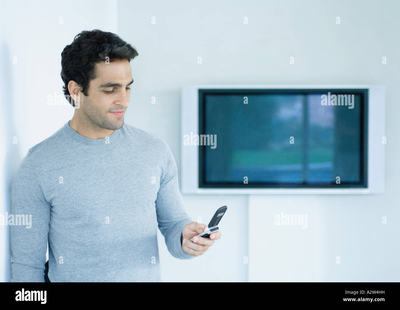 Man standing, looking at cell phone, widescreen TV on wall in background - Stock Image