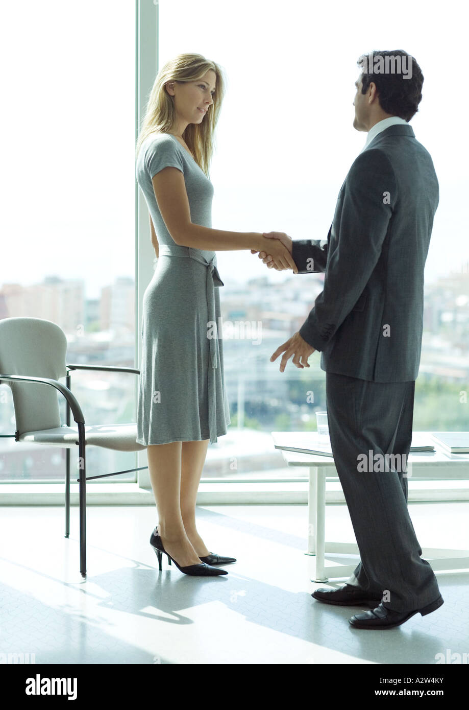 Businessman shaking hands with woman in lobby - Stock Image