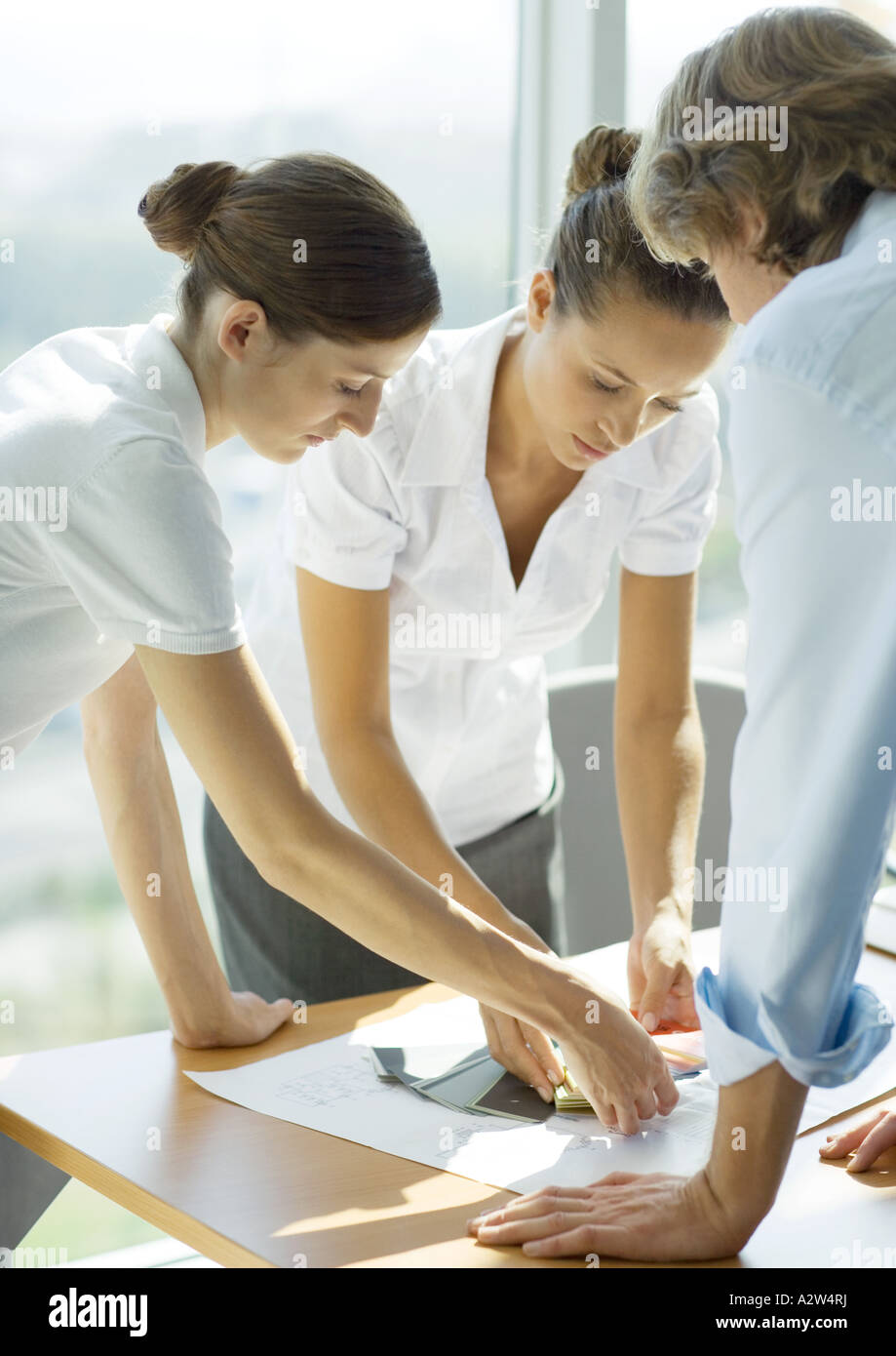 Two female and one male professional looking at color swatches - Stock Image