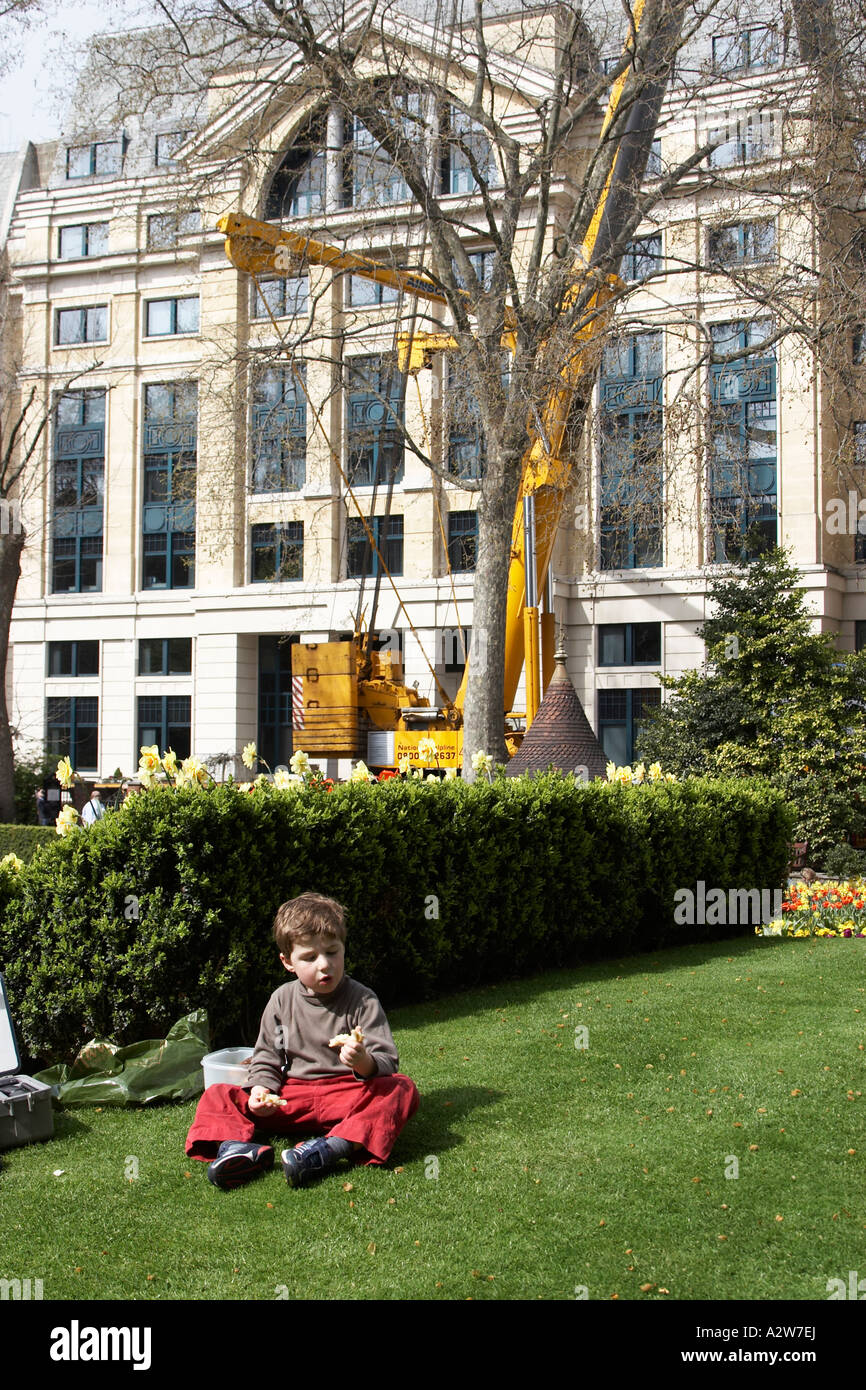 Young boy child sitting on the grass in Finsbury Circus City of London EC2 England NAOH - Stock Image