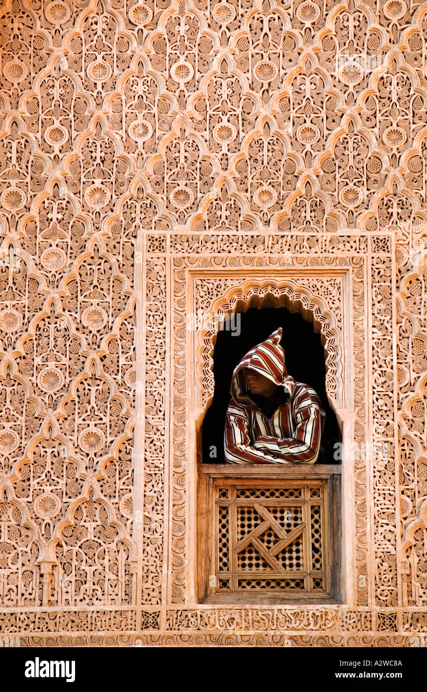 Muslim man looks out of window of student rooms overlooking the courtyard at the theological school of Ali ben Youssef Marrakesh - Stock Image