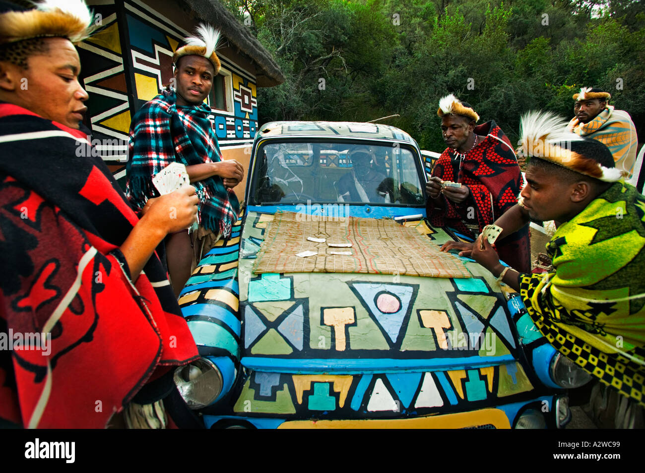 People African men playing cards around an old car Model released Lesedi Cultural Village near Johannesburg South - Stock Image