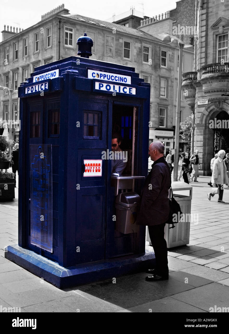 A man buying a drink from an old police box that has been converted into a coffee kiosk, Buchanan street Glasgow - Stock Image