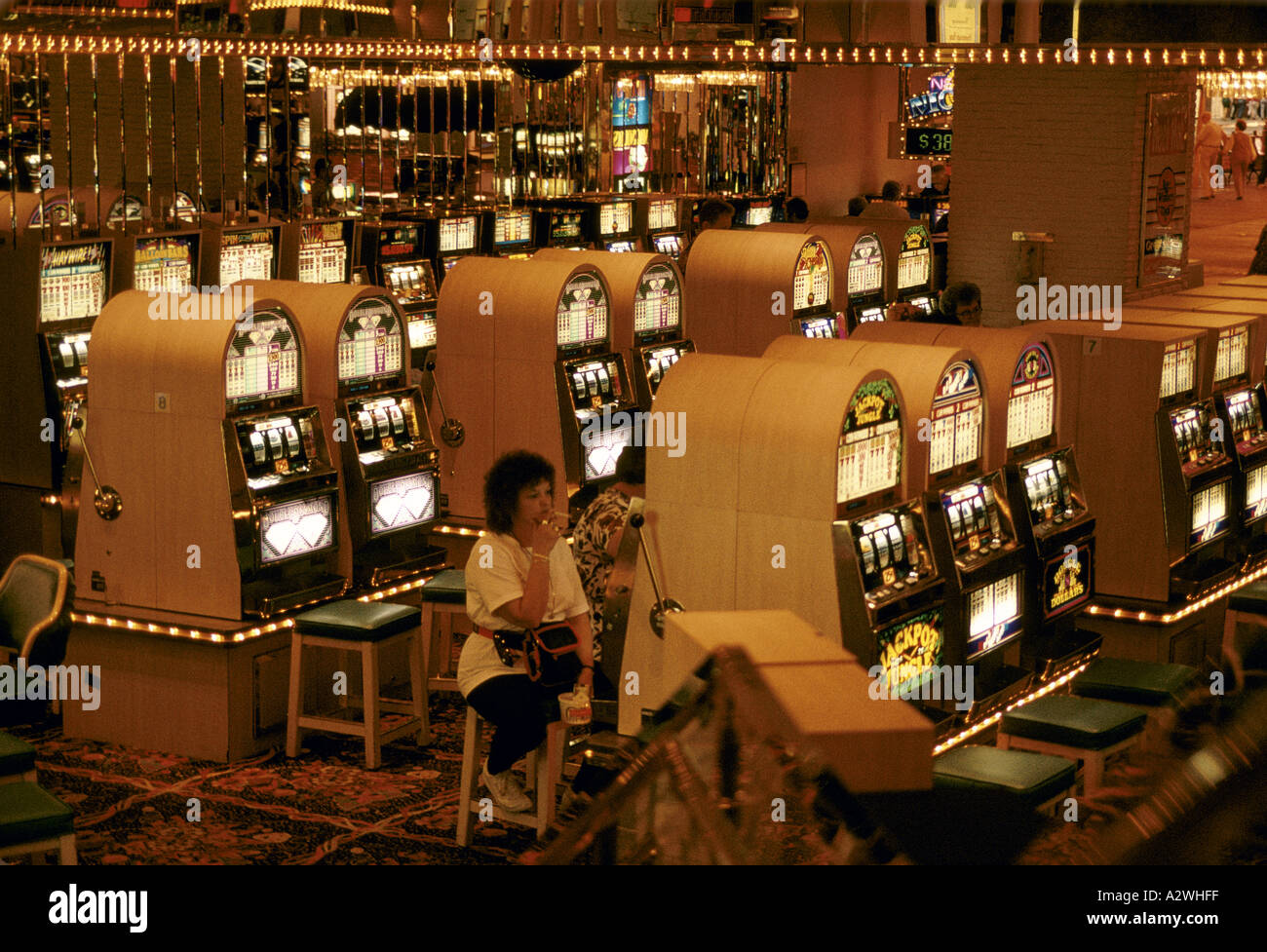 woman smoking cigarette playing slot machines in las vegas ...