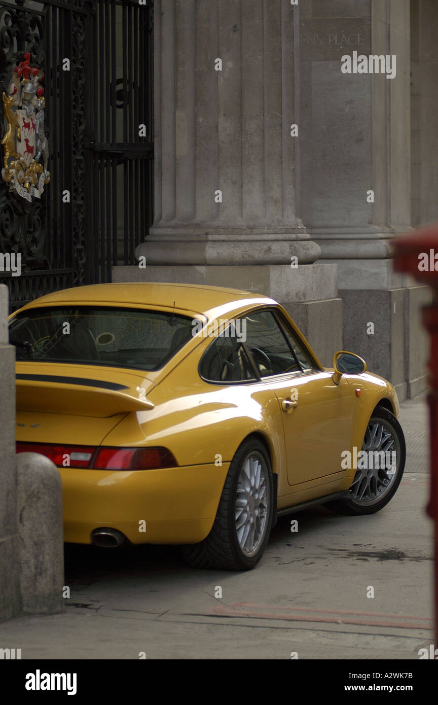 creative parking in the city of london yellow porche sports car parked between the columns in front of bishopsgate - Stock Image
