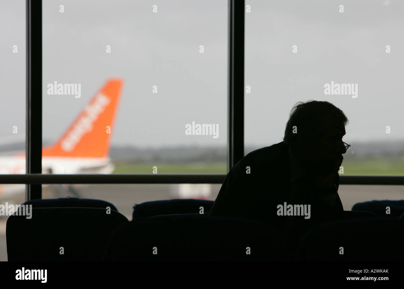 silhouette of businessman on mobile phone in departure lounge with easyjet aircraft in background - Stock Image