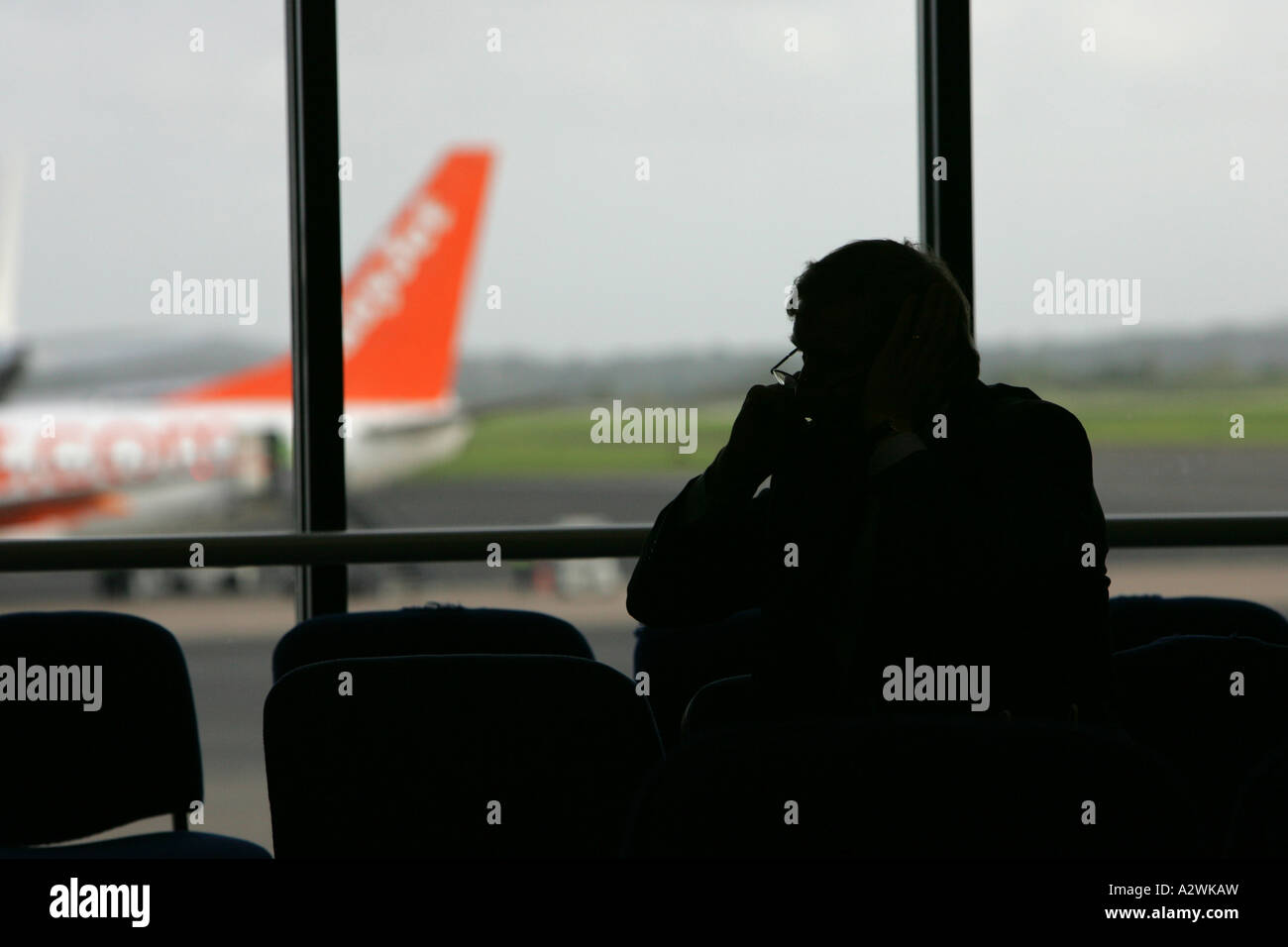 silhouette of businessman on mobile phone in departure lounge with easyjet aircraft in background at Belfast International - Stock Image