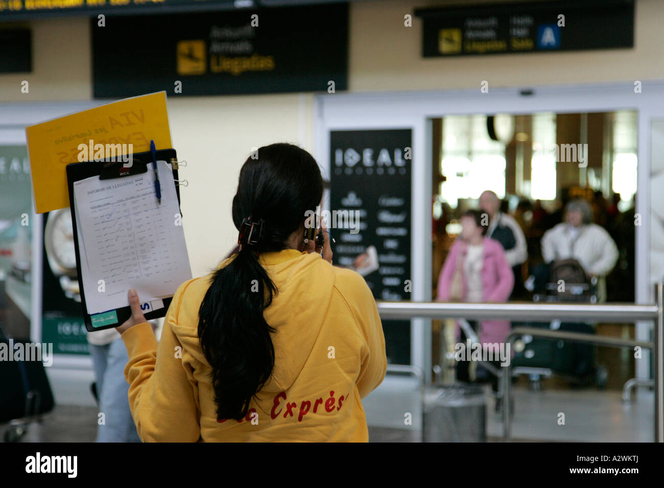 female spanish tour guide in yellow jumper on mobile phone - Stock Image