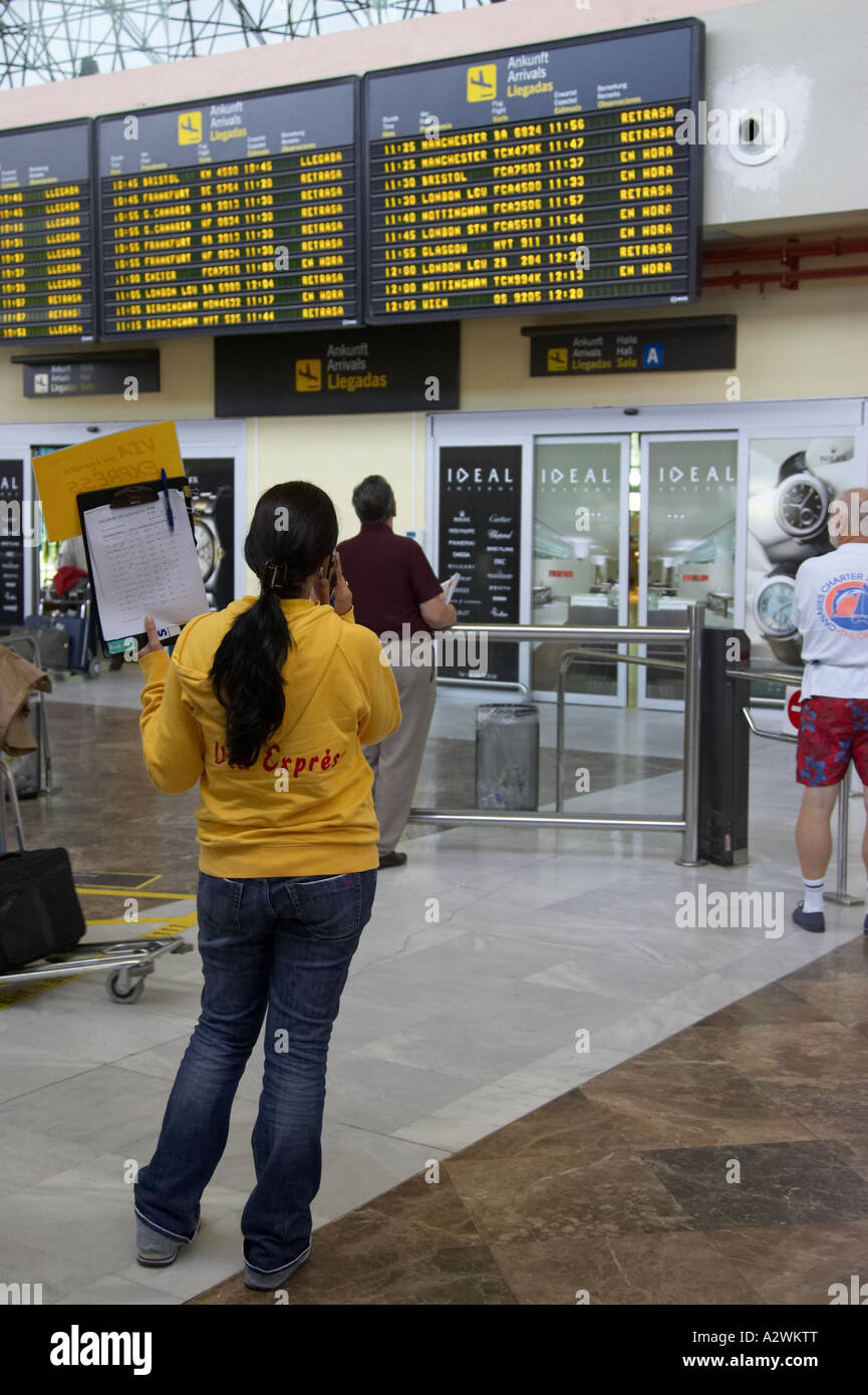 female spanish tour guide in yellow jumper waits in front of arrivals message - Stock Image