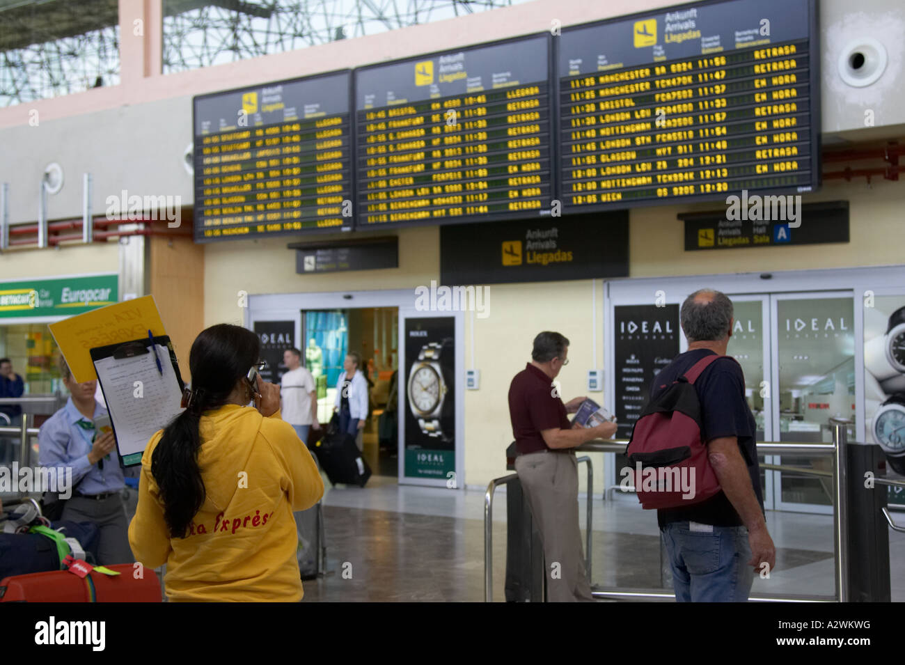 female spanish tour guide in yellow jumper waits in front of arrivals message board with list of passengers at Reina - Stock Image