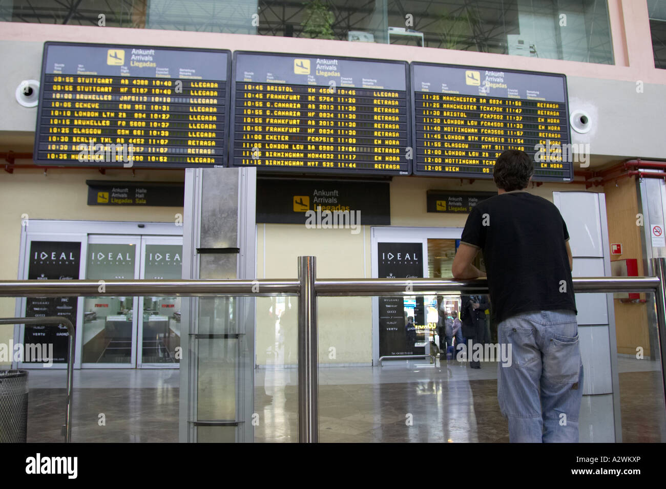 man waits in front of arrivals message board at Reina Sofia Sur TFS South Airport Tenerife Canary Islands Spain - Stock Image