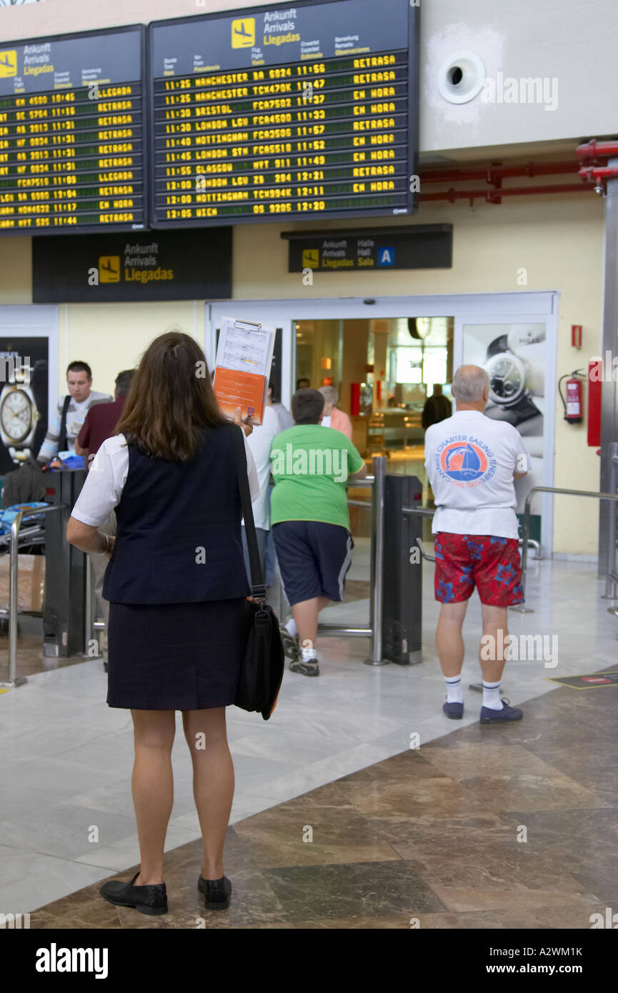 spanish female tour guide waits in front of arrivals message board with list of passengers at Reina Sofia Sur TFS - Stock Image