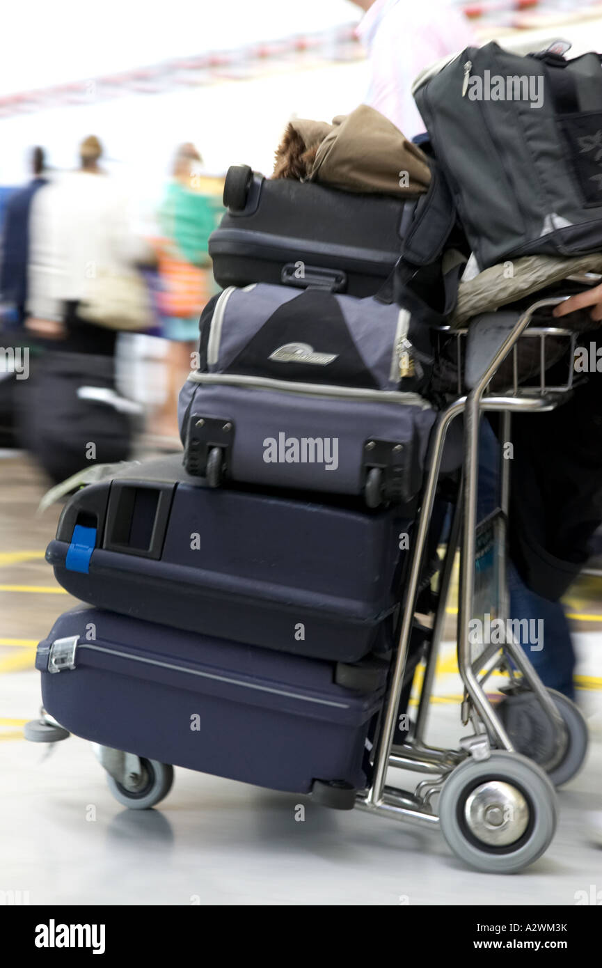 pile of luggage on trolley being pushed out of Reina Sofia Sur TFS South Airport Tenerife Canary Islands Spain - Stock Image