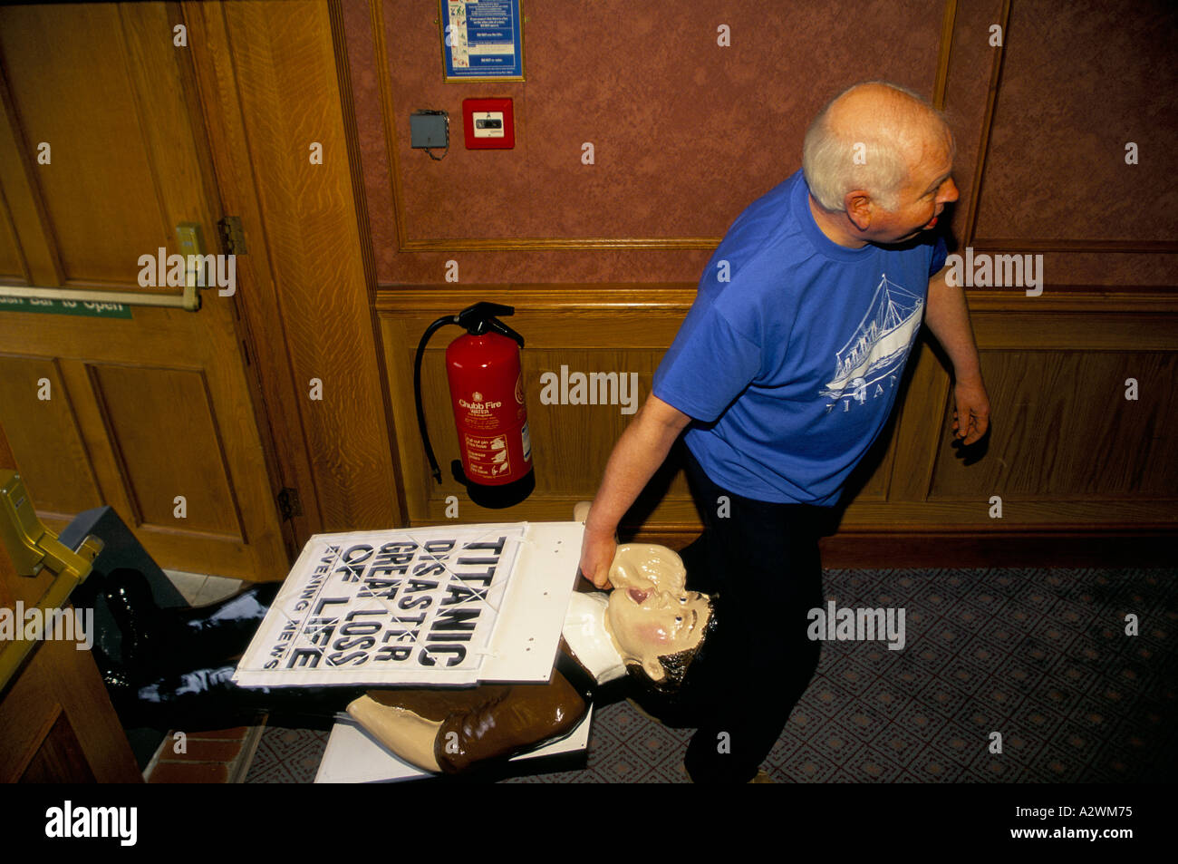 Titanic survivors conference stallholder dragging model of evening news boy carrying placard proclaiming titanic disaster great - Stock Image