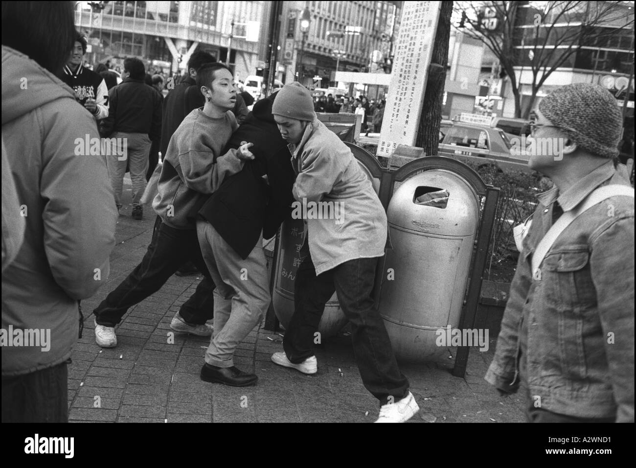 young Japanese men fighting on the street outside the Shibuya train station, Tokyo, Japan - Stock Image