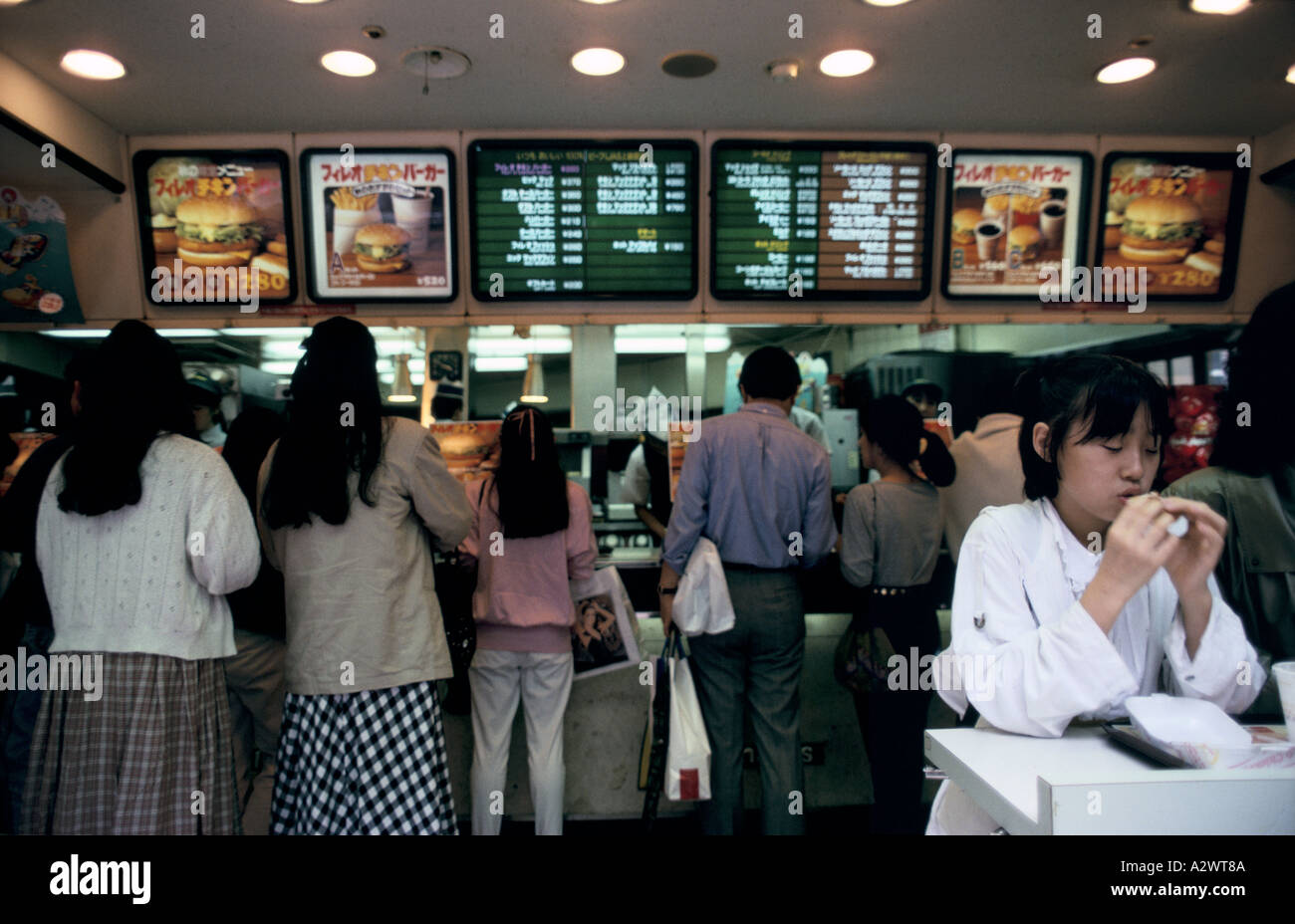 people ordering at the counter of a mcdonalds restaurant tokyo japan - Stock Image