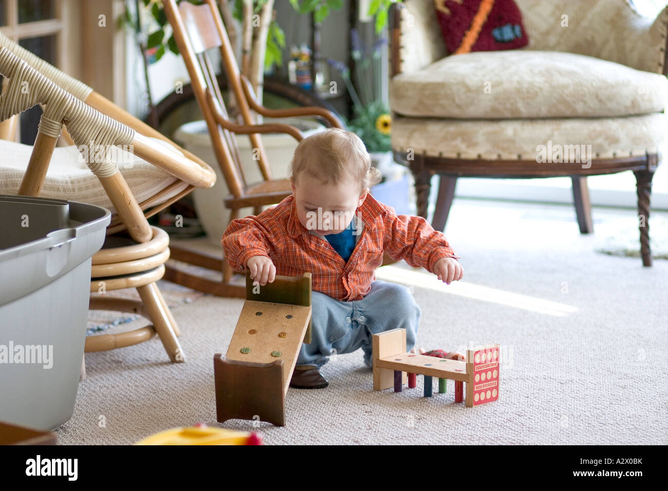 Child toddler playing with pegboard workbench age 1. Plainfield Illinois IL USA - Stock Image