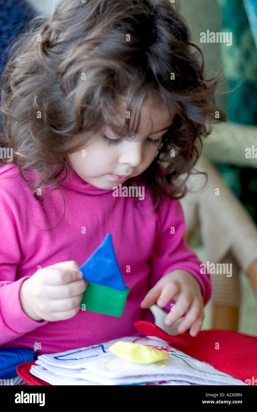 Girl playing with Velcro book age 3. Plainfield Illinois IL USA - Stock Image
